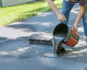 man pouring blacktop sealing on driveway